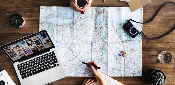 Eine Weltkarte, ein Laptop und Block und Stift zur Reiseplanung.